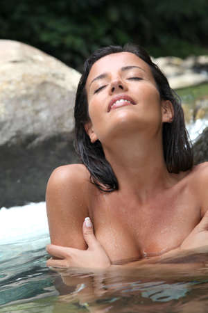 Attractive brunette woman taking a bath in river photo