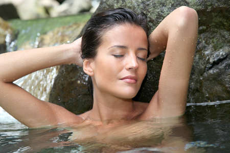 Glamorous woman showering in natural springs photo
