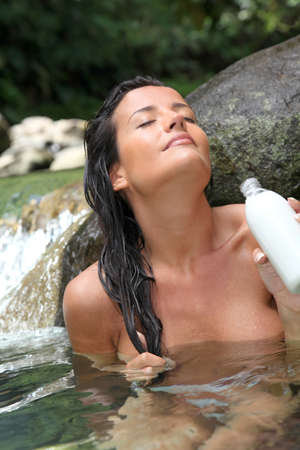 showering: Gorgeous girl in river applying hair conditioner
