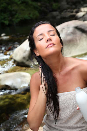 Beautiful young woman applying hair conditioner sitting by river photo