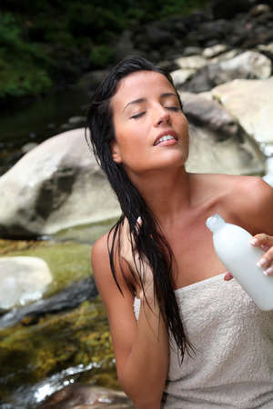 wet hair: Beautiful young woman applying hair conditioner sitting by river