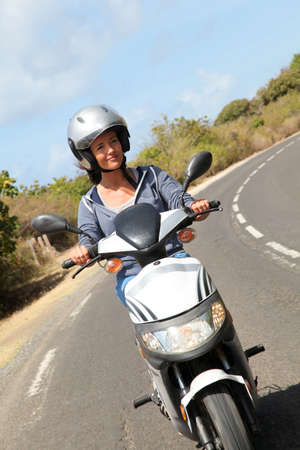 motor scooter: Young woman riding motorbike Stock Photo