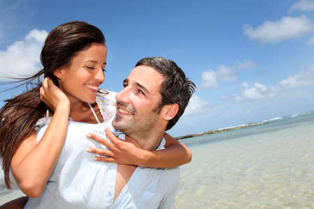 man carrying woman: Lovers enjoying sunny day at the beach