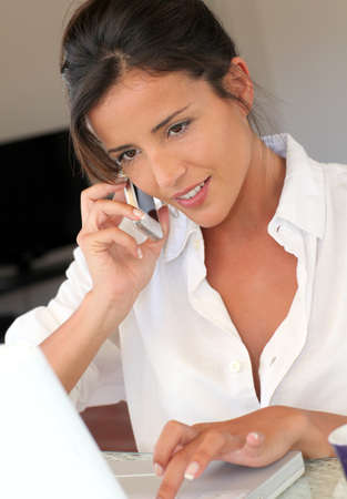 Attractive woman talking on mobile phone in front of laptop photo