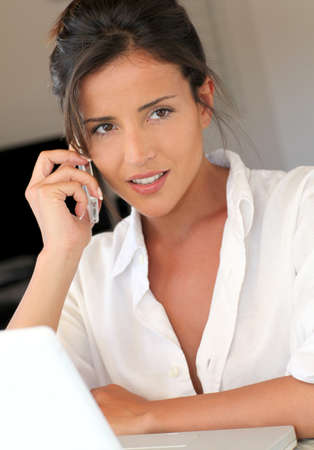 Attractive woman talking on mobile phone in front of laptop Stock Photo - 13122227
