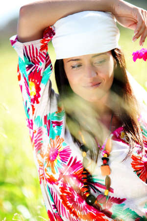 Beautiful gypsy girl with scarf standing in meadow Stock Photo