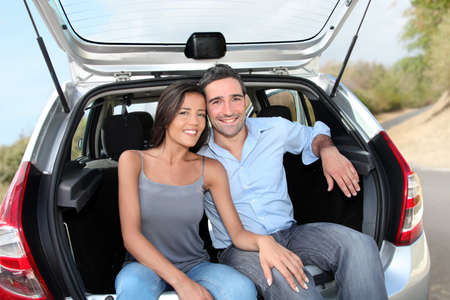 drivers: Happy couple sitting in car open trunk Stock Photo