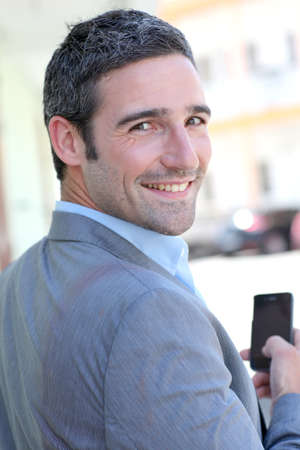 telephone salesman: Businessman using mobilephone out in town
