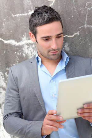 Businessman using electronic tablet outside the office photo