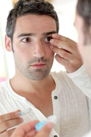 ocular: Man in front of mirrror putting ocular lens