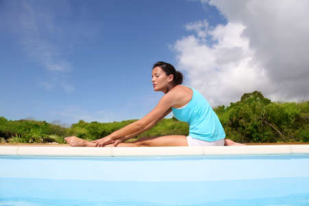 Woman doing stretching exercises by a pool photo