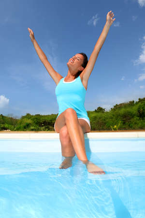Brunette girl in fitness outfit stretching arms by the pool photo