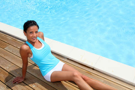 above 25: Brunette girl in fitness outfit relaxing by the pool