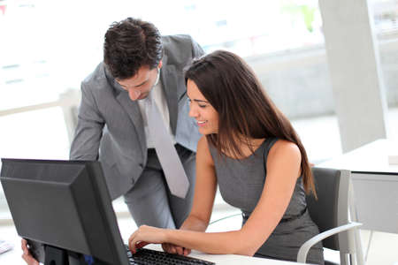 Business people in office working on desktop computer photo