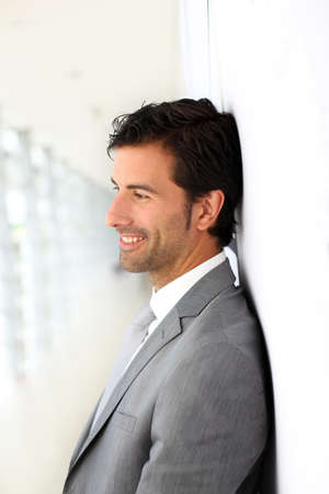 profile view: Businessman standing on white wall- profile view