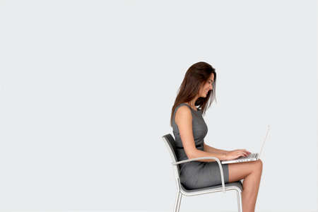 Businesswoman sitting on chair in front of laptop photo