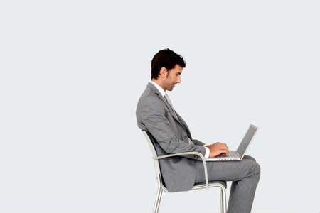 Geschäftsmann sitzt auf Stuhl vor Laptop Standard-Bild - 13262949