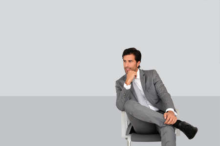 gray suit: Businessman sitting on chair on grey background Stock Photo