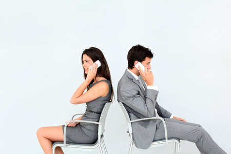 phone conversation: Business people sitting in chairs with mobile phone Stock Photo