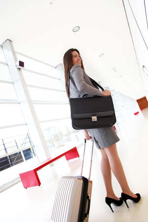 tradeshow: Smiling businesswoman pulling cabin suitcase in hallway Stock Photo