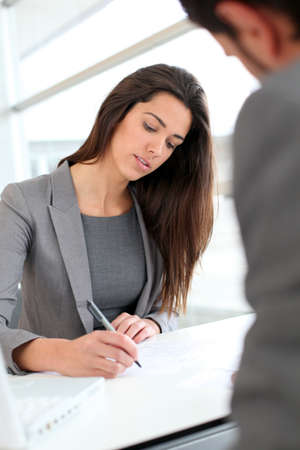 Businesswoman writing on document after meeting photo