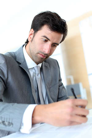 Businessman filling in business contract photo