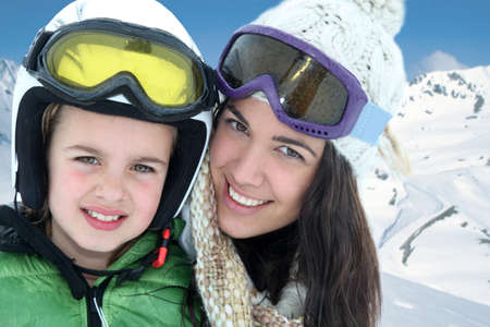 Mother and daughter skiing in the mountain photo