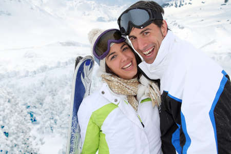 Couple standing on a snowy mountain in ski outfit photo