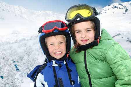 Portrait of children in ski outfit at the mountain photo