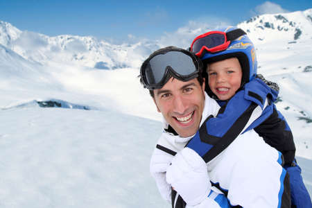 Father carrying son on his back at the mountain photo
