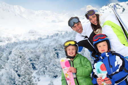 Family of four people at the mountain in winter photo