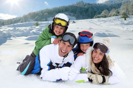 Happy family laying down in the snow photo