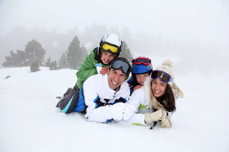 ski mask: Happy family laying down in the snow Stock Photo