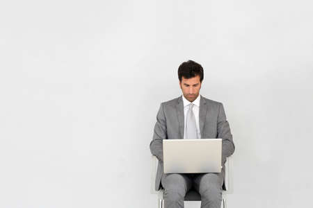 executive chair: Businessman sitting on chair in front of laptop Stock Photo