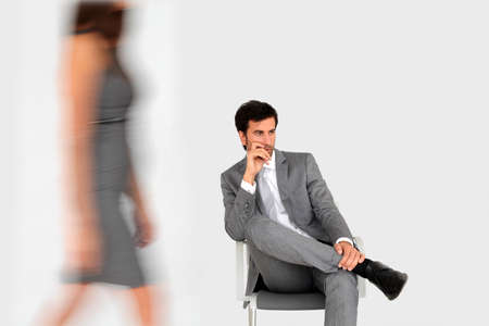 people walking white background: Businessman sitting in waiting room and woman walking by Stock Photo