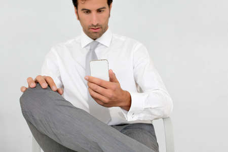 Businessman reading short message on mobile phone photo