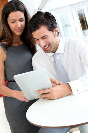 websurfing: Business people websurfing on tablet during breaktime Stock Photo