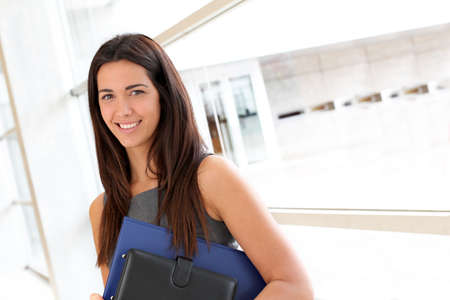 Young businesswoman in modern building holding files photo