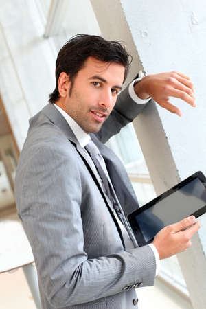 Businessman standing in hall with electronic tablet photo