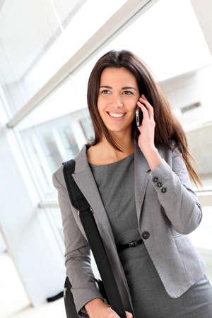 mujer con maleta: Empresaria sonriendo hablando por tel�fono Foto de archivo