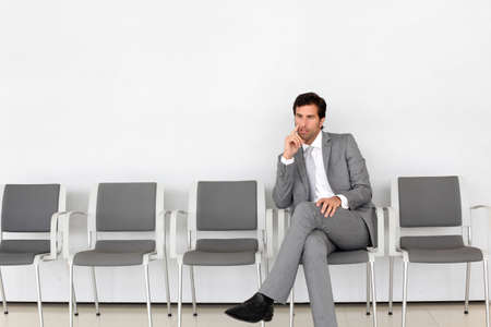 Businessman sitting in airport waiting room photo