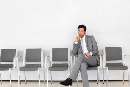 waiting man: Businessman sitting in airport waiting room