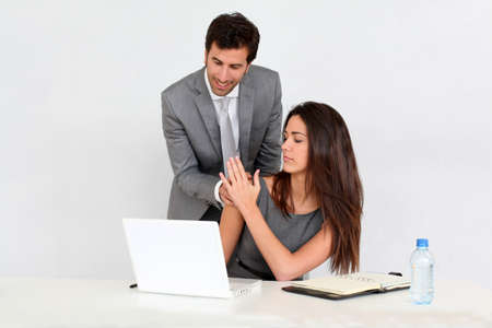 harassing: Businessman in office harassing young woman Stock Photo