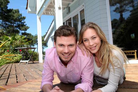 fachada de casa: Retrato de pareja sonriente de pie en frente de la casa Foto de archivo