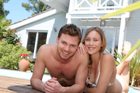Happy young couple relaxing by pool Stock Photo - 13764762