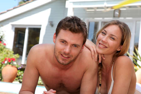 Happy young couple relaxing by pool photo
