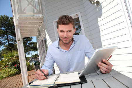 Portrait of smiling man working at home on tablet Stock Photo - 13764883