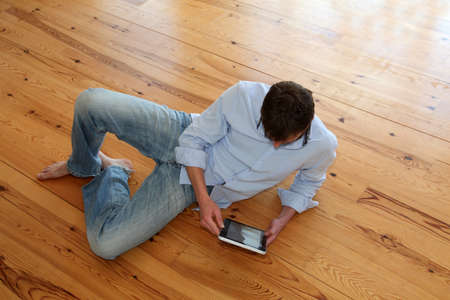 Young man sitting on wooden floor with electronic tablet photo