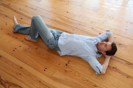 Young man relaxing on wooden floor in apartment photo