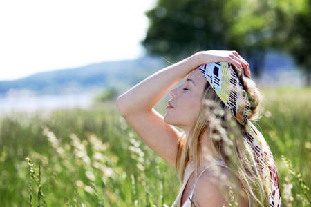 Beautiful blond woman in meadow with modern look photo